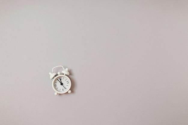 Réveil rétro blanc unique montrant cinq minutes à douze heures sur fond de papier gris avec espace de copie. mise à plat. espace négatif.