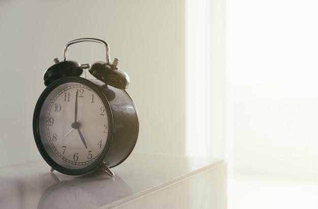 Réveil rétro avec cinq heures du matin ou cinq heures du soir. photo filtre de style vintage.