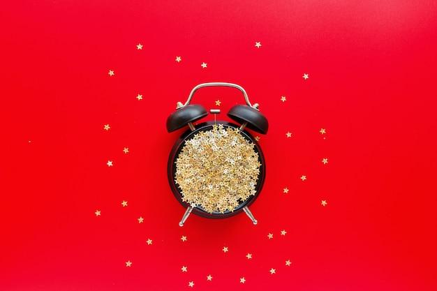 Réveil rétro avec des confettis dorés sur le rouge