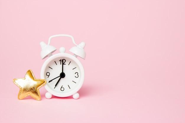 Réveil rétro avec décoration de fête sur fond rose