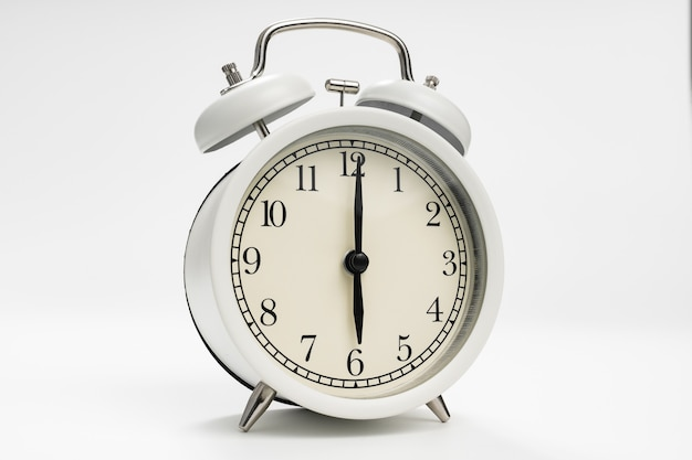 Réveil rétro sur fond blanc. concept d'ascensions tôt le matin. horaire. premier quart de travail à l'école ou au travail.