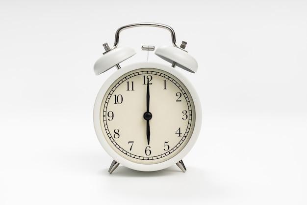 Réveil rétro sur fond blanc. concept d'ascensions tôt le matin.