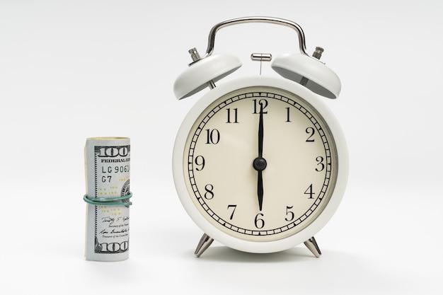 Réveil rétro et une pile de dollars sur fond blanc. investissement conceptuel et littératie financière. premier quart de travail à l'université ou au travail.