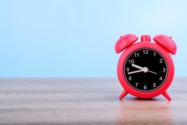 Réveil rétro rouge mis sur table en bois isolé sur fond bleu.