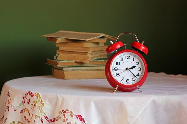 Réveil rétro rouge sur la table avec une nappe blanche.