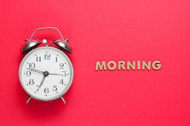 Réveil rétro sur surface rouge avec texte matin avec des lettres.