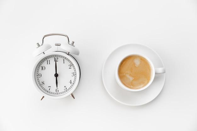 Réveil rétro et une tasse de café sur fond blanc. concept d'ascensions tôt le matin. horaire. premier quart de travail à l'école ou au travail.