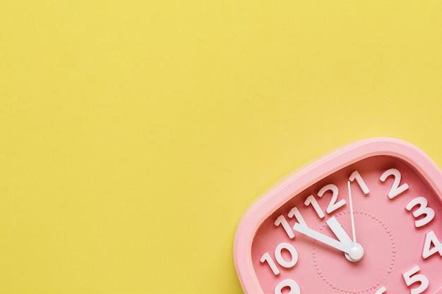 Réveil rose allongé sur fond de surface jaune. vue de dessus.