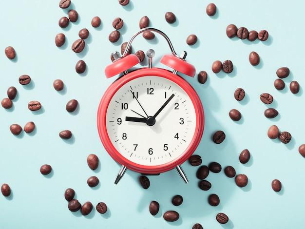 Réveil rouge et grains de café torréfiés sur bleu avec ombre. concept d'éveil matinal, début de journée de travail