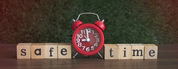 Réveil rouge mis au milieu de safe time écrit sur une cale en bois