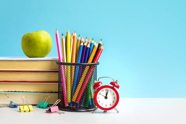 Réveil rouge, pomme, crayons de couleur, livres sur bleu