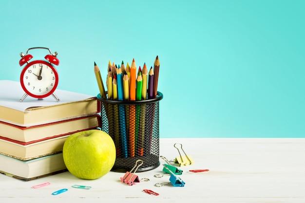 Réveil rouge, pomme, crayons de couleur, livres sur fond bleu