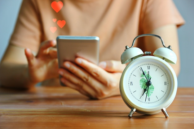 Réveil style vintage devant une femme utilisant un téléphone portable envoie une émotion d'amour