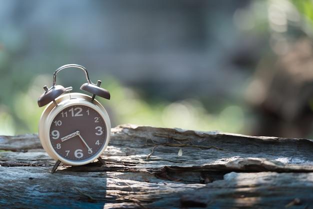 Réveil sur une table en bois avec fond de nature verte bokeh.