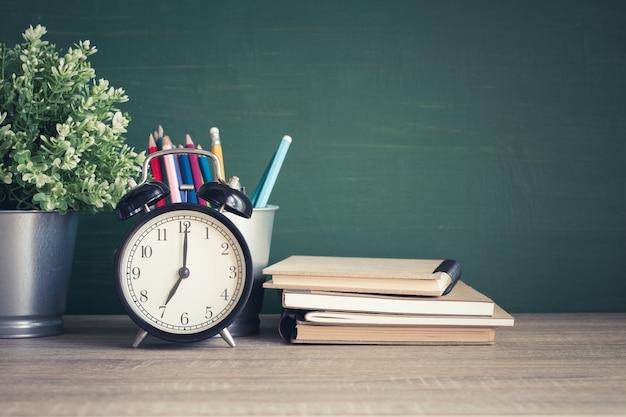Réveil sur table en bois sur fond de tableau noir dans la salle de classe