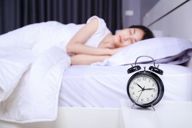 Réveil sur la table et la femme dormir sur le lit dans la chambre