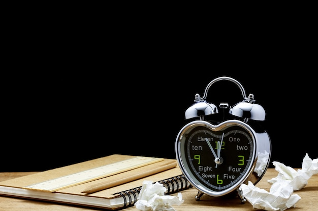 Réveil sur table fond noir, cinq minutes à midi