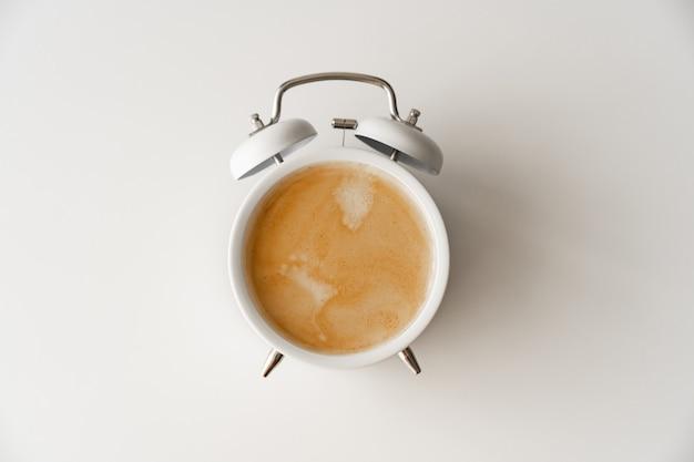 Réveil avec une tasse de café sur fond blanc. concept d'ascensions tôt le matin. premier quart de travail à l'école ou au travail. petit-déjeuner