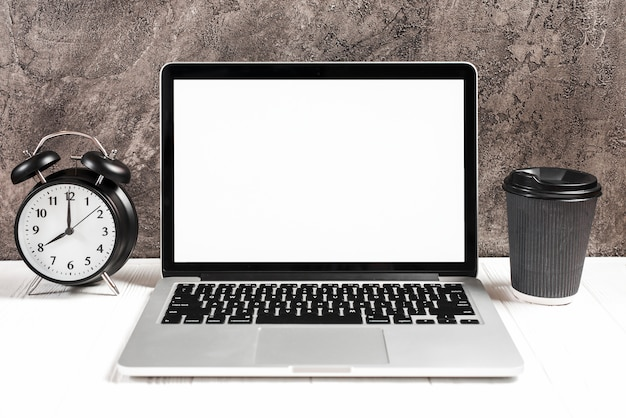 Réveil et tasse à café jetable avec un ordinateur portable ouvert sur un bureau blanc