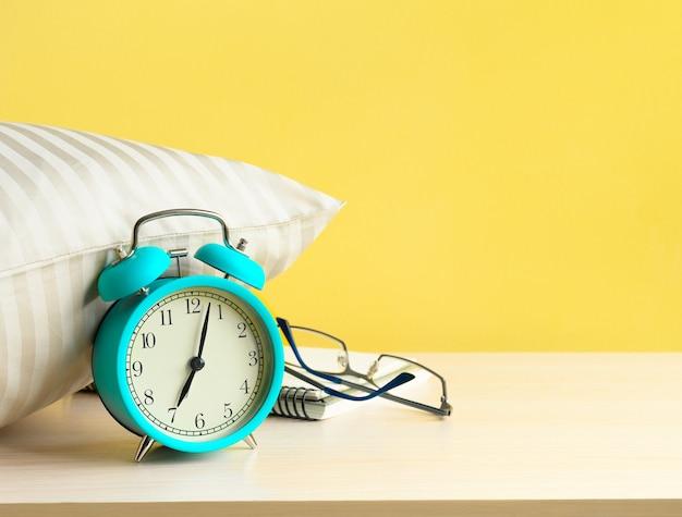 Réveil turquoise du matin près de l'oreiller sur la table de chevet sur fond de mur jaune