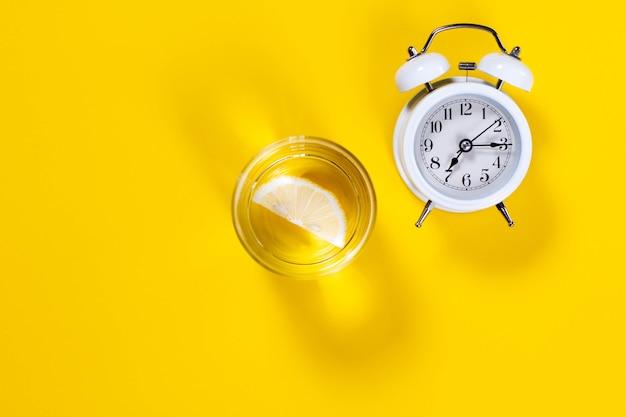 Réveil et un verre d'eau au citron