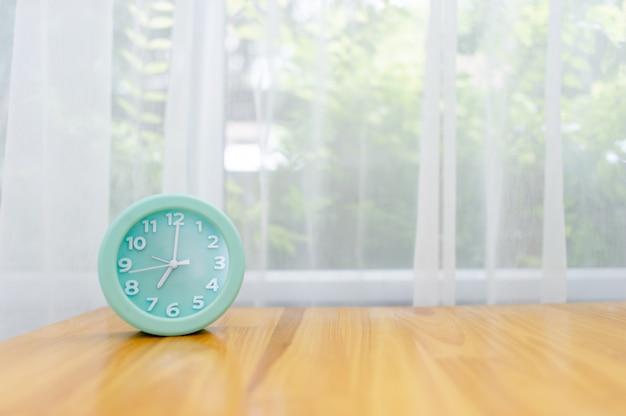 Réveil vert clair posé sur la table de la chambre