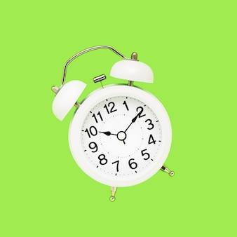 Réveil vintage blanc sur fond vert clair. vue de dessus, copiez l'espace.