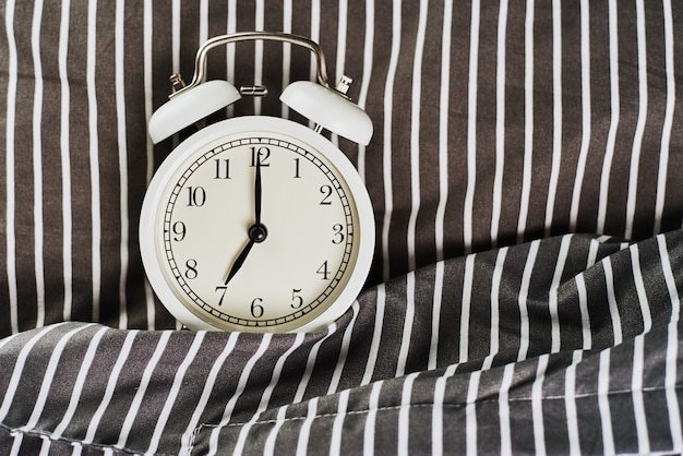 Réveil vintage blanc sur oreiller au lit. wale up et concept du matin