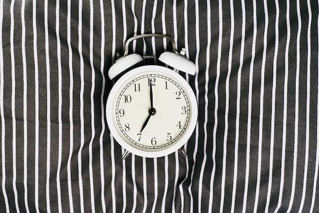 Réveil vintage blanc sur oreiller au lit.