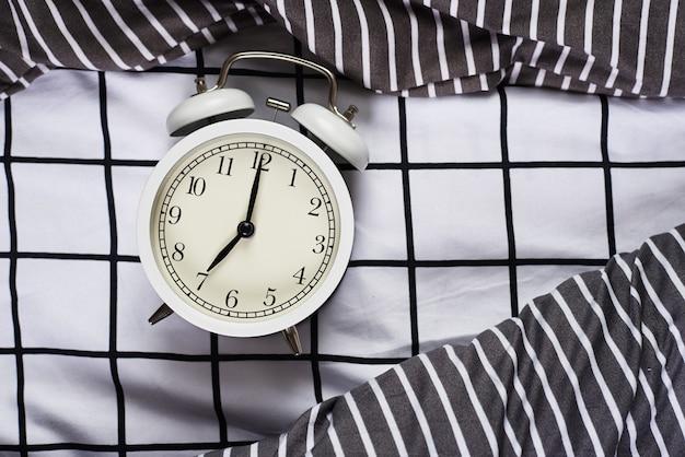 Réveil vintage blanc et oreillers au lit