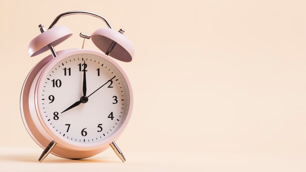 Réveil vintage indiquant l'heure 8'o sur fond beige