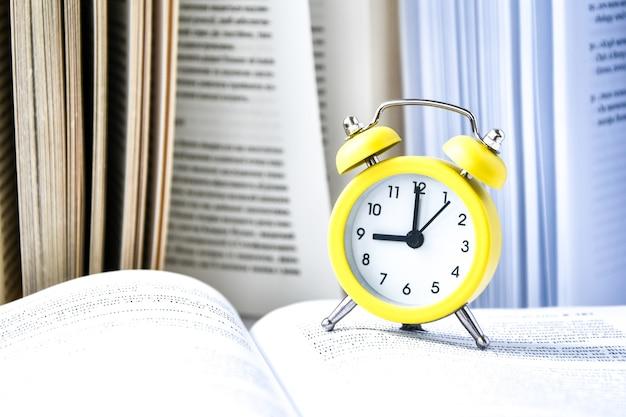 Réveil vintage jaune avec livre sur fond blanc
