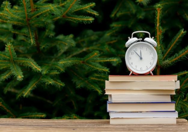 Réveil vintage et livres sur table en bois avec des branches d'épinette sur fond