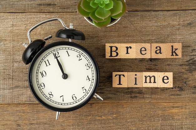 Réveil vintage noir avec un texte break time sur un fond de planche de bois minable mise à plat