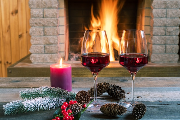Réveillon de noël. deux verres de vin et bougie près d'une cheminée confortable, dans une maison de campagne.