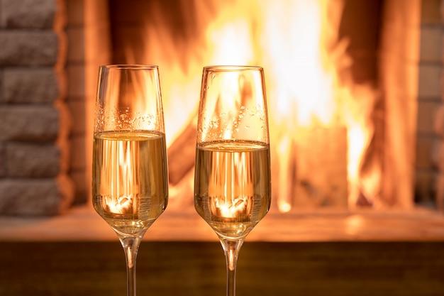 Réveillon de noël. deux verres de vin près de la cheminée, dans une maison de campagne.
