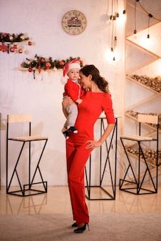 Réveillon de noël. mère de famille et bébé dans santa hatplay game à la maison près de la cheminée.