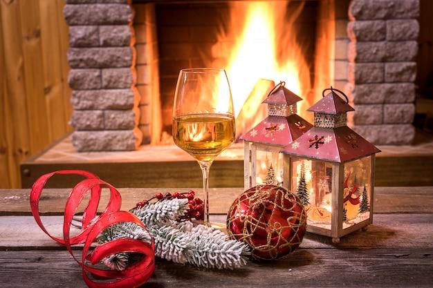 Réveillon de noël. verre de vin et lanternes de noël près d'une cheminée confortable, dans une maison de campagne.