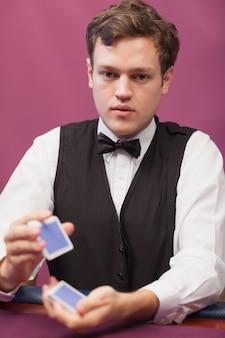 Revendeur assis dans un casino en battant des cartes