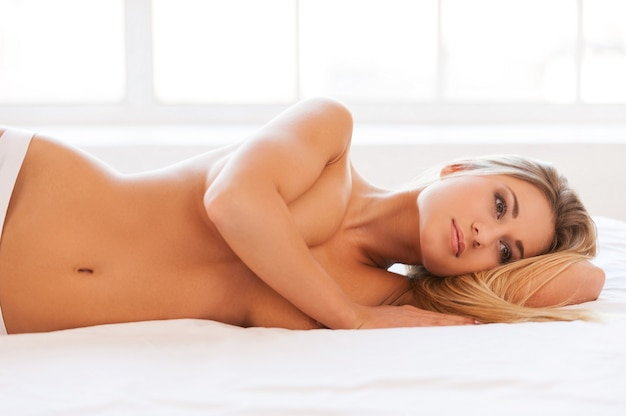 Rêver de beauté. belle jeune femme torse nu en culotte allongée dans son lit et couvrant les seins avec la main