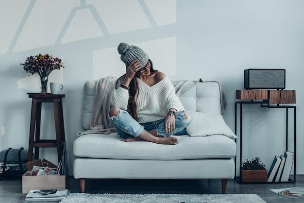 Rêver de beauté. jolie jeune femme en tenue décontractée et bonnet en tricot tenant la main sur la tête