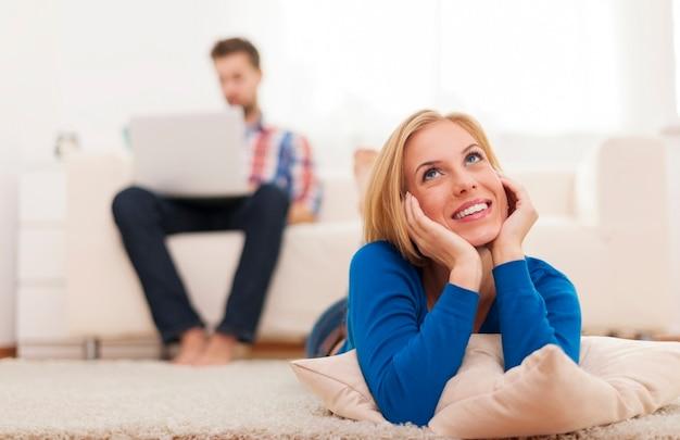Rêver de femme allongée sur un tapis à la maison
