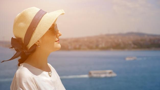 Rêver de femme en chapeau de soleil se tient à moitié face en profitant de vacances et en regardant au loin contre un paysage flou en gros plan copyspace