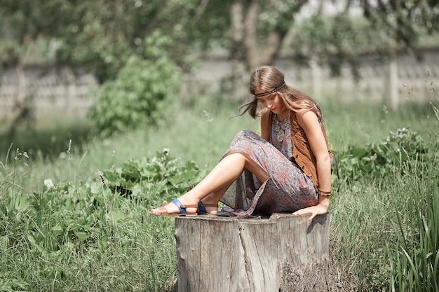 Rêver de femme hippie assise sur une grosse souche dans un parc de la ville