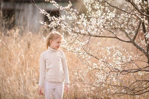 Rêver fille blonde dans les vêtements blancs dans le jardin de fleurs près des fleurs blanches de sakura.