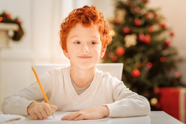 Rêver grand. enfant aux cheveux bouclés radieux à la recherche de vacances avec un sourire joyeux sur son visage tout en pensant et en écrivant une lettre au père noël.