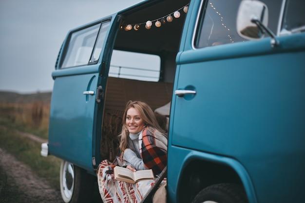 Rêver de... jolie jeune femme recouverte d'une couverture en détournant les yeux et souriante assise à l'intérieur de la mini-fourgonnette bleue de style rétro