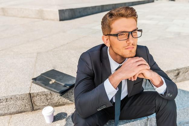 Rêver de jour d'homme d'affaires. vue de dessus d'un jeune homme réfléchi en tenue de soirée, tenant la main sur le menton et regardant ailleurs alors qu'il était assis à l'extérieur