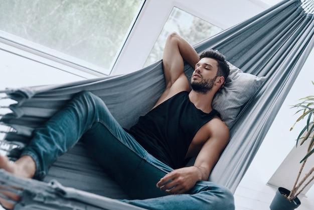 Rêver de jour. vue de dessus du beau jeune homme en vêtements décontractés dormant en position couchée dans le hamac à l'intérieur