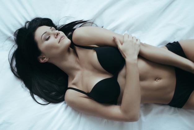 Rêver de lui. vue de dessus de jolie jeune femme en lingerie noire posant de manière séduisante